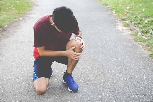 Perto do homem do esporte, sofrendo com dor nos esportes em execução lesão no joelho após a execução. lesão do conceito de treino.