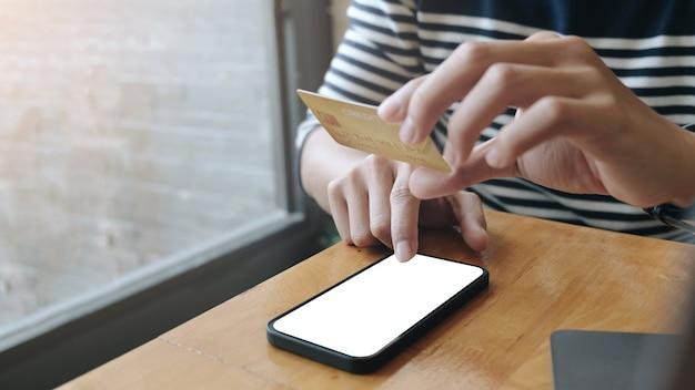 Perto do homem está as mãos segurando um telefone celular e um cartão de crédito com tela de espaço de cópia em branco para sua mensagem de texto de publicidade ou conteúdo promocional, compras online.