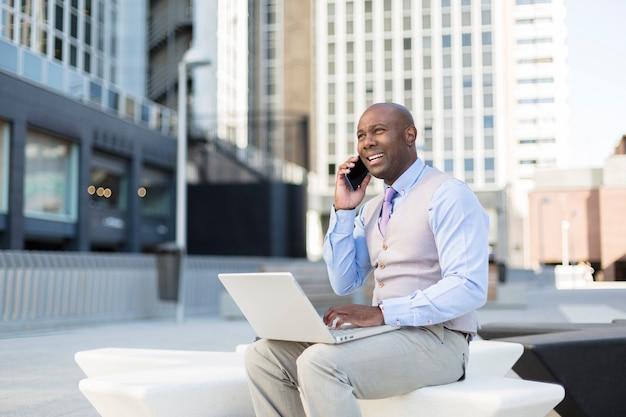 Perto do homem negro empreendedor, trabalhando com seu laptop na rua.