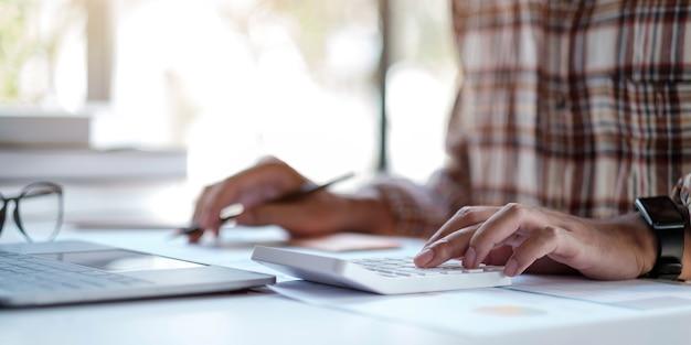 Perto do homem ou mão do contador segurando a caneta trabalhando na calculadora para calcular o relatório de dados financeiros, documento contábil e laptop no escritório.