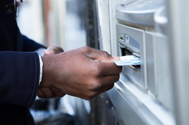 Perto do homem tirando dinheiro do caixa eletrônico com cartão de crédito.