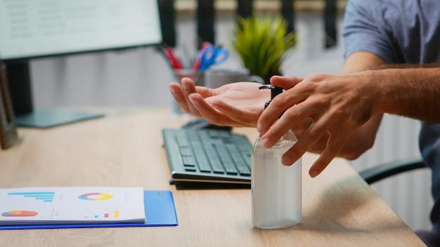 Perto do homem usando gel antibacteriano antes de escrever no computador. empreendedor que trabalha em um novo local de trabalho de escritório normal de empresa, limpando, desinfetando as mãos com álcool desinfetante contra o vírus corona.