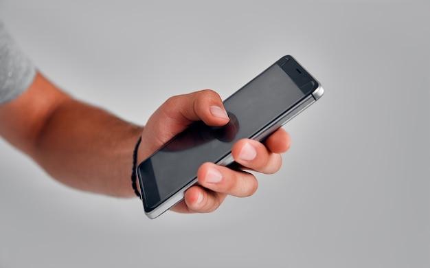 Perto do homem usando o smartphone. conceito de dependência de telefone. homem de negócios jovem digitando e navegando nas mídias sociais em seu telefone.