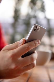 Perto do homem usando telefone móvel inteligente isolado na parede branca. estilo de vida, conceito de tecnologias modernas.