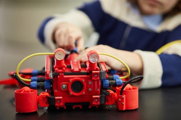 Perto do irreconhecível menino menino construindo uma máquina robótica vermelha enquanto desfruta da aula de engenharia na escola de desenvolvimento, copie o espaço