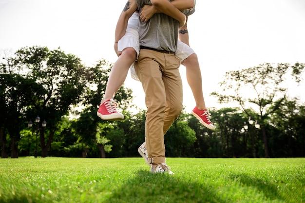 Perto do jovem casal bonito, regozijando-se no parque.