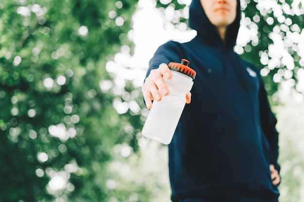 Perto do jovem corredor com capuz segurando uma garrafa de água enquanto faz exercícios no sol de verão