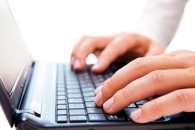 Perto do jovem empresário trabalhando em um laptop isolado no fundo branco