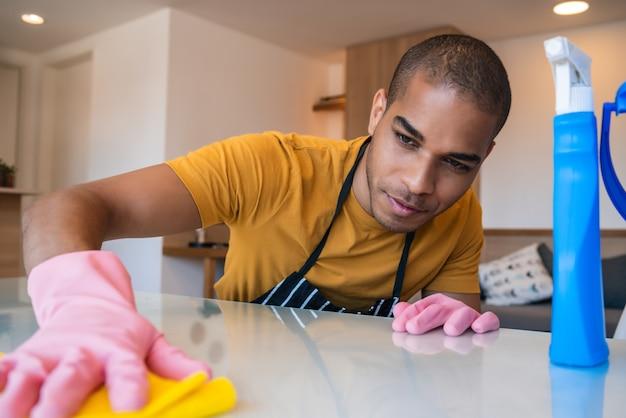Perto do jovem latino, limpando as manchas da mesa em casa. conceito de arrumação e limpeza.