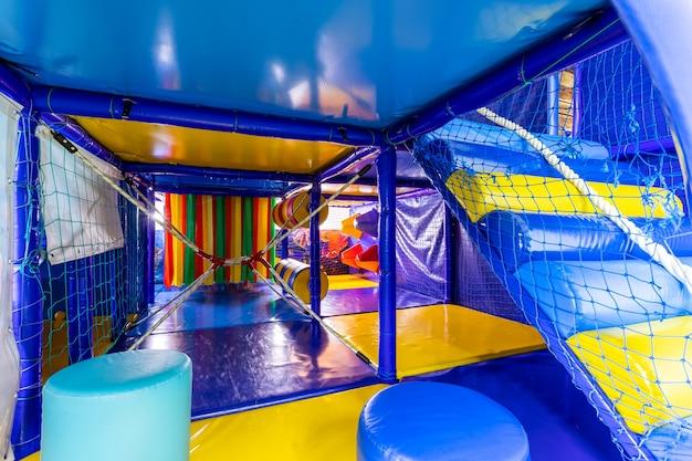 Perto do labirinto azul e amarelo do grande castelo inflável no playground