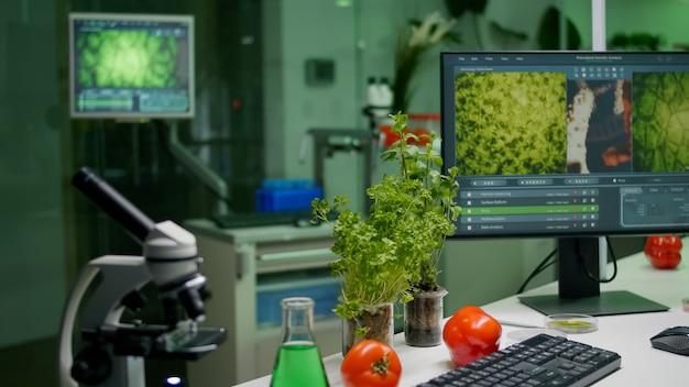 Perto do laboratório de pesquisa científica com microscópio de frasco de tubos de ensaio de vidro e mudas