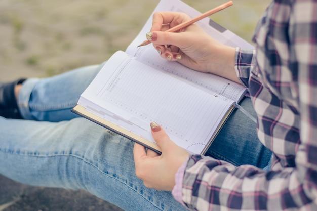 Perto do lápis e do bloco de notas das mãos da mulher
