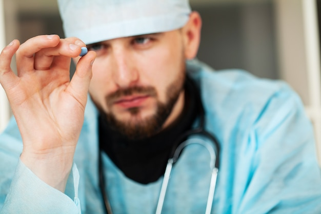 Perto do médico masculino segurando a pílula para a saúde dos homens.