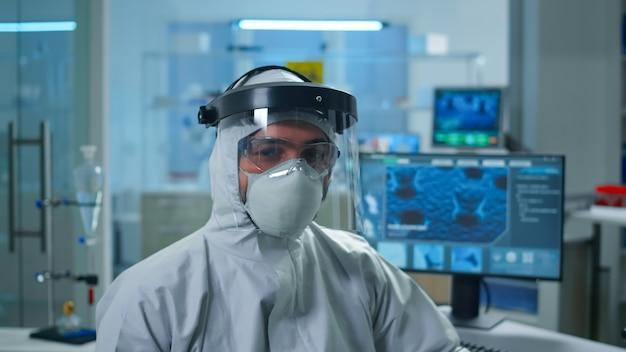Perto do médico, químico, cansado, de macacão, olhando para a câmera, trabalhando em um laboratório científico equipado