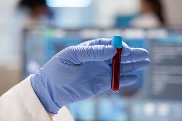 Perto do médico segurando uma amostra de sangue em vaccutainer. orolog em laboratório profissional analisando a evolução de vacinas, usando tecnologia moderna, epidemias, inovação em saúde.