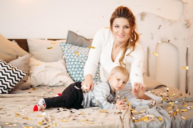 Perto do menino bonito e positivo com a linda mãe em um estúdio decorado com estilo