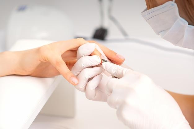 Perto do mestre de manicure com pinça de manicure corta cutículas de unhas femininas no salão de beleza.