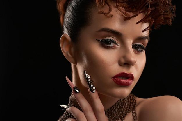 Perto do modelo com arte de unhas na moda e maquiagem brilhante.