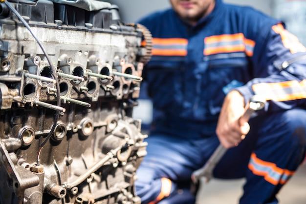 Perto do motor do carro e do mecânico na oficina.