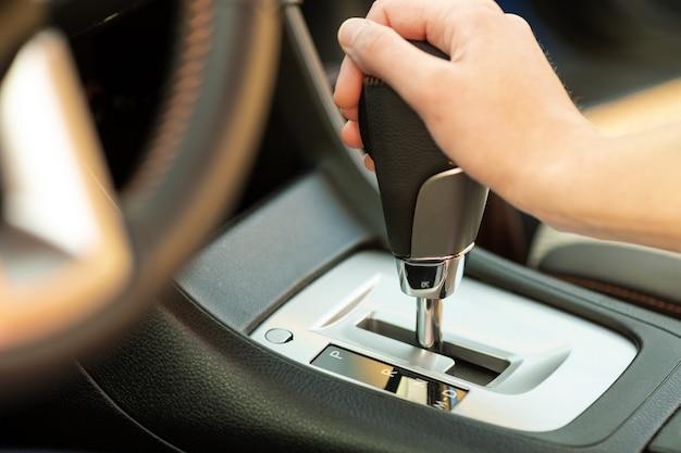 Perto do motorista da mulher segurando a mão dela na alavanca de mudança automática, dirigindo como um carro.