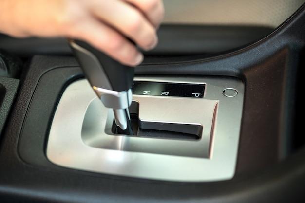 Perto do motorista mulher segurando a mão dela na alavanca de mudança automática, dirigindo como um carro.