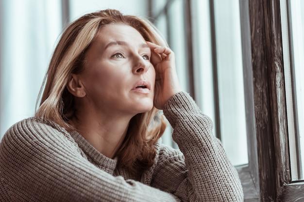 Perto do peitoril da janela. linda e agradável mulher madura de suéter em pé perto do peitoril da janela