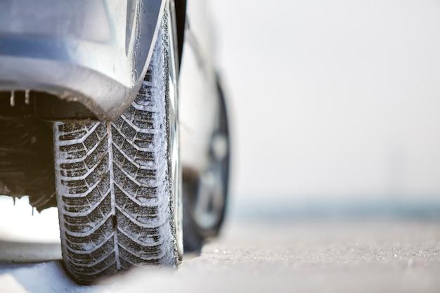 Perto do pneu de borracha das rodas do carro na neve profunda