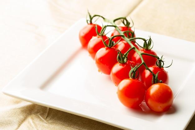 Perto do prato quadrado branco em cima da mesa com um ramo de saborosos tomates cereja vermelhos maduros