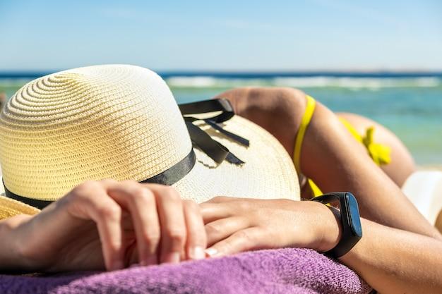Perto do quadril de mulher jovem e ombro deitado na cadeira de praia em banhos de sol da costa do mar.