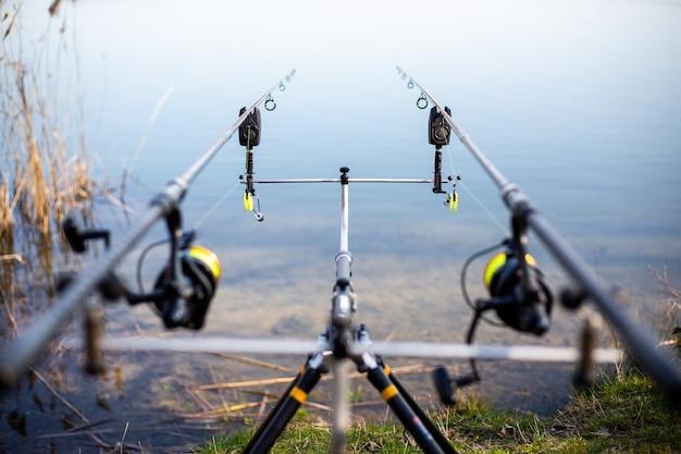 Perto do rack com varas de pesca à beira do lago, pescador esperando peixes de água doce, pesca, pesca esportiva
