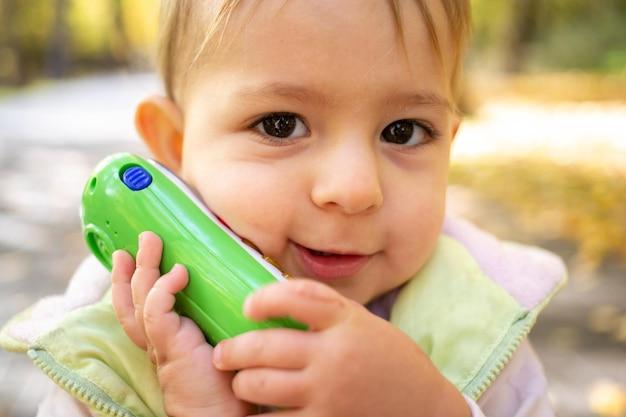 Perto do retrato de uma criança fofa brincando e falando em um telefone de brinquedo