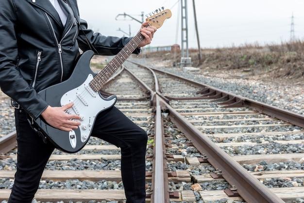 Perto do rocker com óculos de sol tocando guitarra elétrica nos trilhos do trem abandonado.