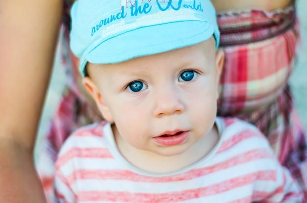 Perto do rosto de bebê menino de olhos azuis com a boca aberta e boné azul. criança e conceito de emoções de crianças.