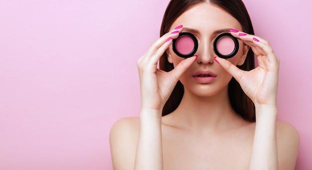 Perto do rosto de mulher jovem e bonita com a pele limpa, perfeita com sombra rosa, blush.