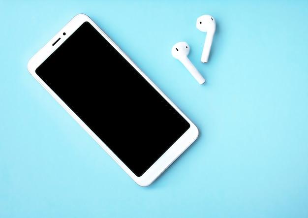 Perto do smartphone com fones de ouvido em fundo azul