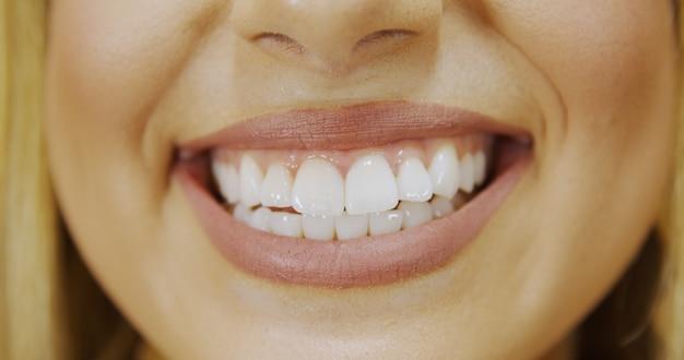 Perto do sorriso com dentes brancos e saudáveis. o sorriso largo e bonito de uma mulher jovem e fresca com dentes brancos e grandes e saudáveis