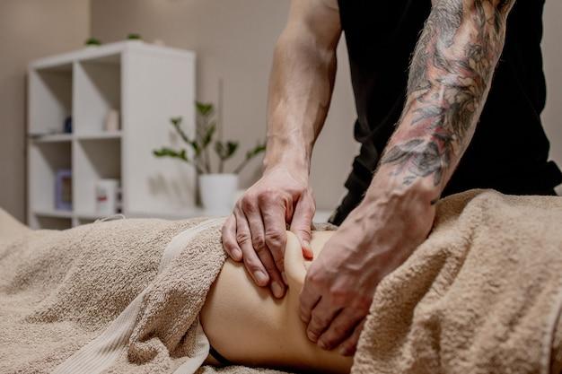 Perto do terapeuta fazendo massagem abdominal na mulher no spa.