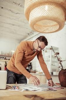 Perto do trabalho. designer de moda focado na escolha das cores para sua nova coleção fica na mesa com amostras.