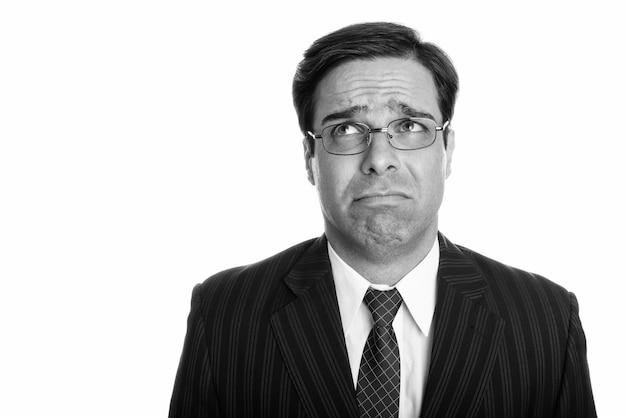 Perto do triste jovem empresário persa pensando enquanto olha para cima com óculos isolados