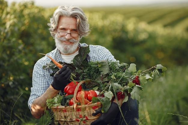 Perto do velho fazendeiro segurando uma cesta de legumes. o homem está parado no jardim. sênior em um avental preto.