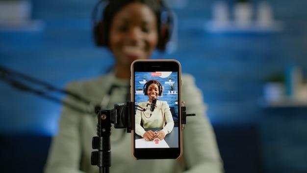 Perto do vlog de gravação de smartphone do influenciador africano em estúdio caseiro usando o smartphone. falando durante a transmissão ao vivo, blogueiro discutindo em podcast usando fones de ouvido e microfone profissional