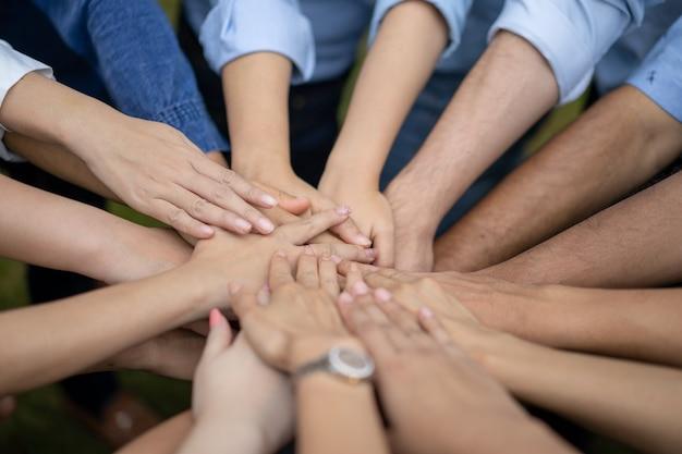 Perto dos asiáticos, os asiáticos se dão as mãos no meio de seu grupo, amigo com pilha de mãos mostrando o amor e a comunidade de bons amigos.