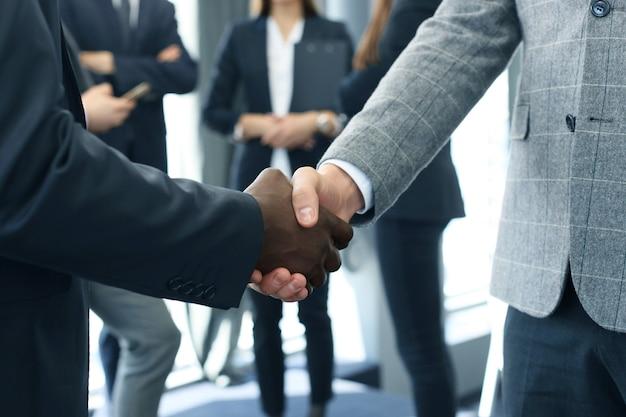Perto dos empresários apertando as mãos.