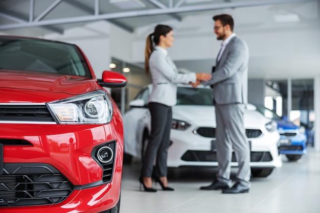Perto dos faróis de um carro. vendedor de carros e cliente apertando as mãos.