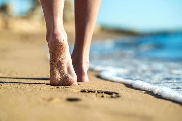 Perto dos pés de uma mulher andando descalça na areia, deixando pegadas na praia dourada