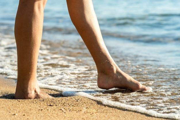 Perto dos pés de uma mulher caminhando descalça na praia de areia na água do mar