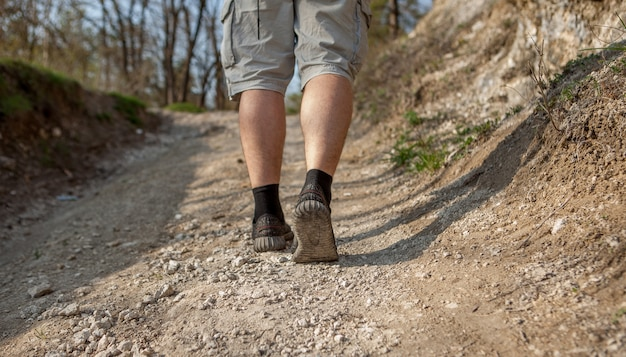 Perto dos pés do homem no caminho da floresta