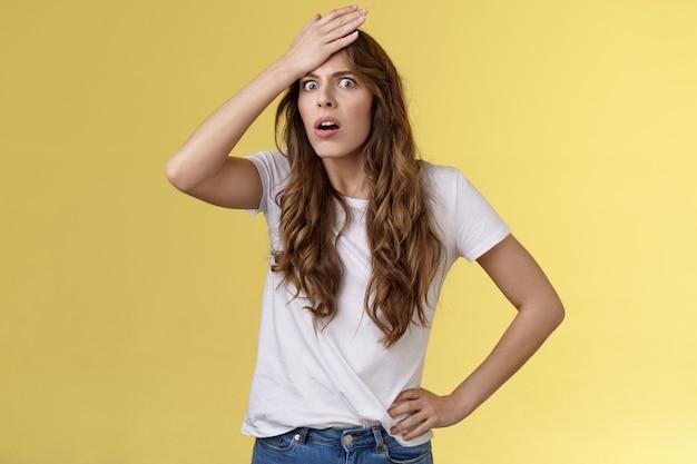 Perturbada, angustiada, incomodada, chocada, garota de cabelo encaracolado percebendo cometer um erro estúpido soco na testa ofegante encolhimento careta incomodada face palmas chateada lembre-se de tarefa importante