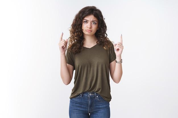 Perturbado chateado decepcionar jovem fofa namorada armênia mal-humorada apontando dedos levantados para cima franzindo a testa fazendo beicinho desapontado reclamando expressar humor sombrio sem interesse, fundo branco em pé