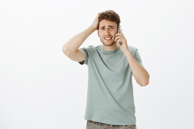 Perturbado e perturbado, um modelo masculino bonito com cabelo claro, franzindo a testa e cerrando os dentes, tocando o cabelo, segurando o smartphone perto da orelha, ouvindo notícias terríveis e ficando triste